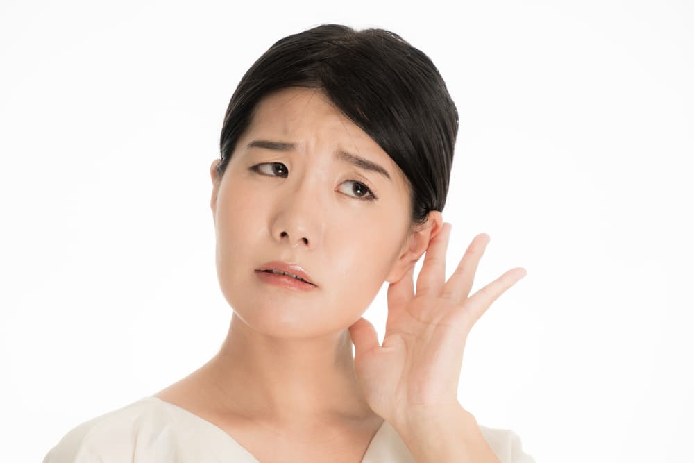 Woman cupping her ear with her hand and straining to listen